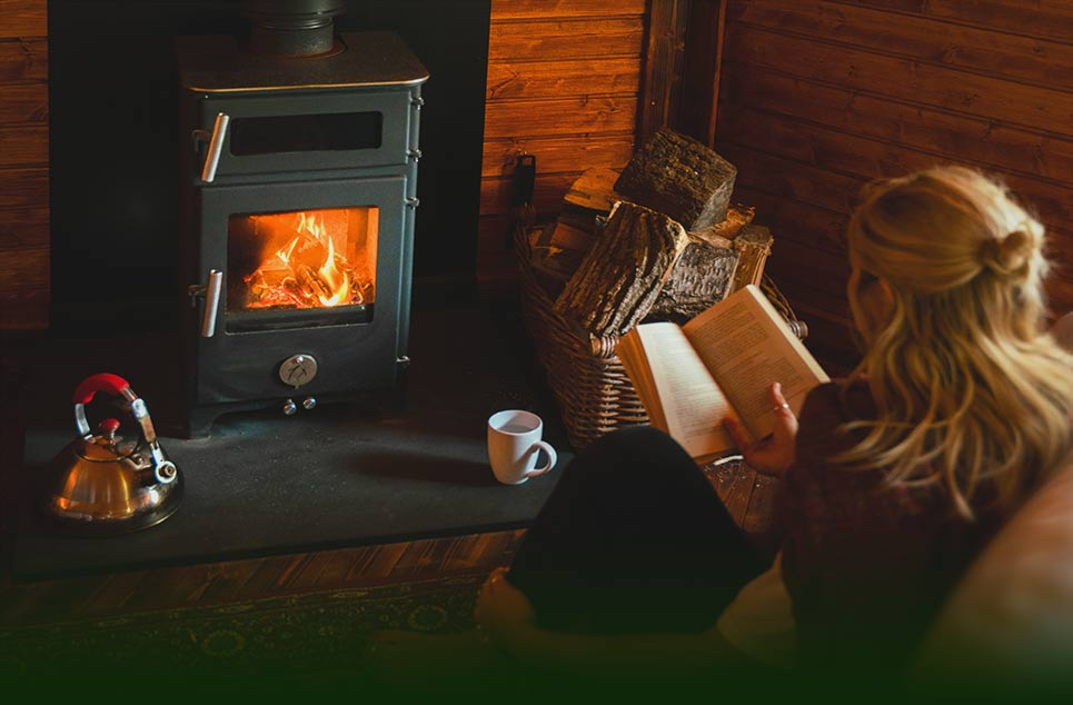 Woman reading her book sitting by a log fire inside the Cabin